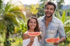 Portrait des couples heureux mangeant l'homme gai et la femme de pastèque ensemble tenant la tranche de pastèque dehors plus de Photographie stock libre de droits