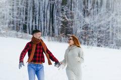 Portrait des couples heureux riant et tenant des mains tout en courant le long du pré neigeux pendant les chutes de neige Photo libre de droits