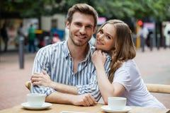 Portrait des couples heureux se reposant au café de trottoir Photos stock