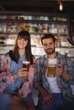 Portrait des couples heureux tenant des verres de bière au compteur Photo stock