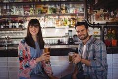 Portrait des couples heureux tenant des verres de bière au compteur Photos libres de droits