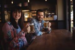Portrait des couples heureux tenant des verres de bière au compteur Photos stock