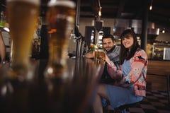 Portrait des couples heureux tenant des verres de bière au compteur Images libres de droits