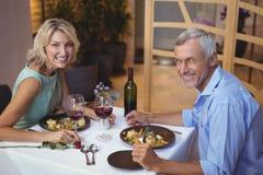 Portrait des couples mûrs ayant le dîner et le vin rouge Photographie stock libre de droits