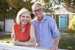 Portrait des couples mûrs regardant au-dessus de la barrière d'arrière cour Photographie stock