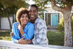 Portrait des couples mûrs regardant au-dessus de la barrière d'arrière cour images stock