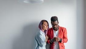 Portrait des couples multiraciaux heureux d'isolement au-dessus du fond gris de mur, l'espace de copie Photographie stock libre de droits