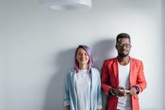Portrait des couples multiraciaux heureux d'isolement au-dessus du fond gris de mur, l'espace de copie Images stock