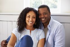 Portrait des couples romantiques détendant dans la chaise à la maison photographie stock