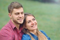 Portrait des couples romantiques se reposant sur l'herbe, la lecture anticipée et le sourire Image libre de droits