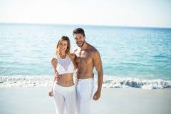 Portrait des couples se tenant avec le bras autour sur le rivage Images stock