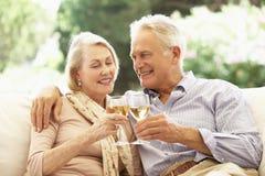 Portrait des couples supérieurs détendant sur Sofa With Glass Of Wine Photographie stock