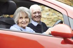 Portrait des couples supérieurs de sourire pour la commande dans la voiture Photos stock