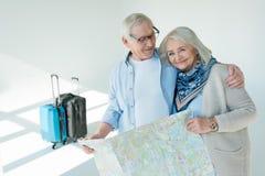Portrait des couples supérieurs de sourire tenant la carte de déplacement Photos stock
