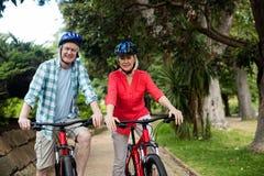 Portrait des couples supérieurs se tenant avec la bicyclette en parc Photographie stock