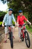 Portrait des couples supérieurs se tenant avec la bicyclette en parc Photos libres de droits