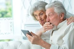 Portrait des couples sup?rieurs heureux utilisant le comprim? image libre de droits