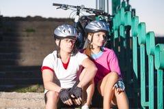 Portrait des cyclistes caucasiens dans l'équipement de sport posant avec le vélo Photographie stock libre de droits
