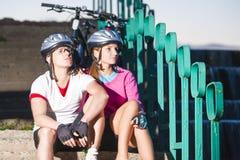 Portrait des cyclistes caucasiens dans l'équipement de sport posant avec le vélo Image stock