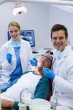 Portrait des dentistes examinant un patient masculin avec des outils photo stock