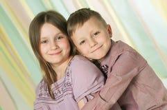 Portrait des deux enfants de mêmes parents étreignants au-dessus du fond vert-jaune dépouillé Photo stock