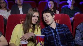 Portrait des deux jeunes dans une salle de cinéma, ils parlent et observent un film banque de vidéos