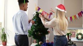 Portrait des employés de bureau de sourire heureux décorant peu d'arbre de Noël artificiel portant le chapeau et les cerfs commun banque de vidéos