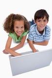 Portrait des enfants à l'aide d'un carnet tout en se trouvant sur le plancher Images stock