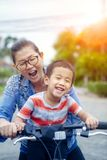 Portrait des enfants asiatiques montant la bicyclette avec émotion de sourire de bonheur de visage de mère images libres de droits
