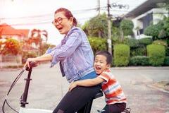 Portrait des enfants asiatiques montant la bicyclette avec émotion de sourire de bonheur de visage de mère photo stock