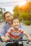 Portrait des enfants asiatiques montant la bicyclette avec émotion de sourire de bonheur de visage de mère image libre de droits