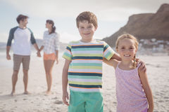 Portrait des enfants de mêmes parents de sourire avec des parents se tenant dans le backgeround Images stock