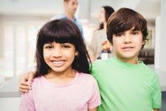 Portrait des enfants de mêmes parents de sourire se tenant à la table Photos libres de droits