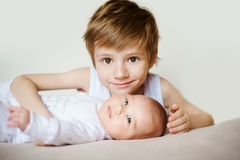 Portrait des enfants de mêmes parents heureux mignons jeune garçon tenant son bébé infantile Photos stock