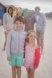 Portrait des enfants de mêmes parents heureux se tenant avec des parents à l'arrière-plan Images stock