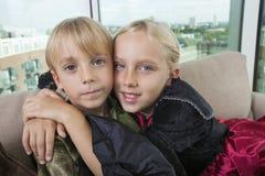 Portrait des enfants de mêmes parents mignons dans des costumes de dinosaure et de vampire à la maison Image stock