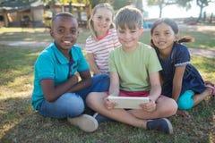 Portrait des enfants de sourire s'asseyant au parc Photographie stock