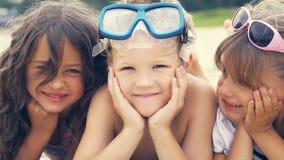 Portrait des enfants de sourire se trouvant sur la plage en été Deux filles heureuses et garçon Photo stock