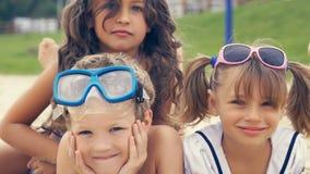 Portrait des enfants de sourire se trouvant sur la plage en été Les petites filles étreint leur frère Photo stock