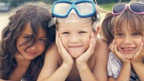 Portrait des enfants de sourire se trouvant sur la plage en été Les petites filles étreint leur frère Images libres de droits