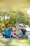 Portrait des enfants gais avec des bras autour de se reposer au parc Image stock