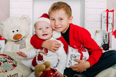 Portrait des enfants heureux avec des boîte-cadeau et des décorations de Noël Deux enfants ayant l'amusement à la maison Photographie stock