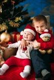 Portrait des enfants heureux avec des boîte-cadeau et des décorations de Noël Deux enfants ayant l'amusement à la maison Images libres de droits