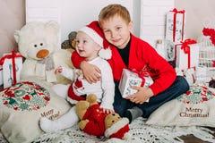 Portrait des enfants heureux avec des boîte-cadeau et des décorations de Noël Deux enfants ayant l'amusement à la maison Image stock