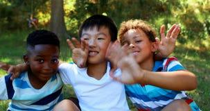 Portrait des enfants heureux ondulant des mains en parc banque de vidéos