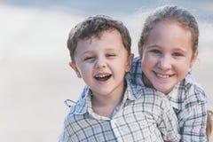 Portrait des enfants heureux près d'une maison au temps de jour Image stock