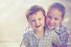 Portrait des enfants heureux près d'une maison au temps de jour Photo stock