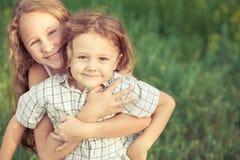 Portrait des enfants heureux qui se tenant en parc au jour Image libre de droits