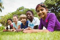 Portrait des enfants heureux se trouvant sur l'herbe Images stock