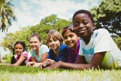 Portrait des enfants heureux se trouvant sur l'herbe Photos libres de droits